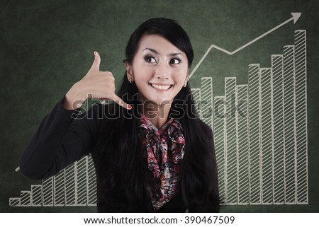 Businesswoman gesturing phone call in front of business chart - stock photo