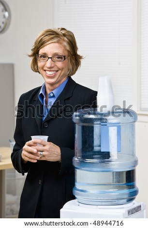 Businesswoman getting water from water cooler - stock photo