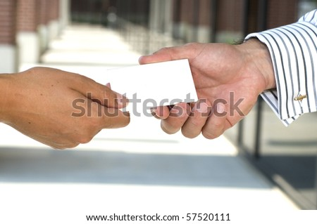 Businesswoman giving a business card to a man - stock photo