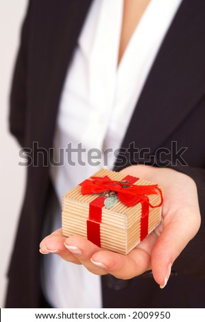 businesswoman giving a gift, shallow dof - stock photo