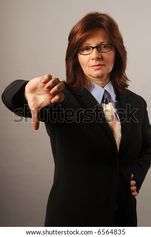 Businesswoman giving a thumbs down to the deal - stock photo