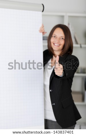 Businesswoman giving a thumbs up gesture of approval and success while standing alongside a blank white flipchart - stock photo