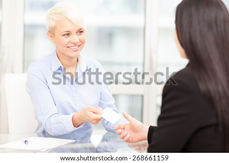 Businesswoman giving her business card to another businesswoman in office - stock photo