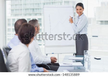 Businesswoman giving presentation in front of her colleagues in bright office - stock photo