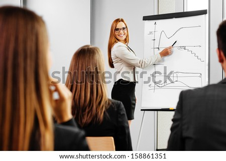 Businesswoman giving presentation on flipchart. Business meeting in the office - stock photo