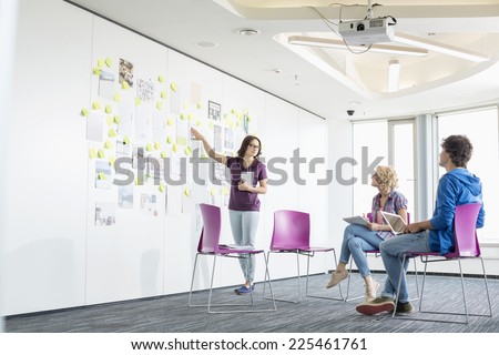Businesswoman giving presentation to colleagues in creative office space