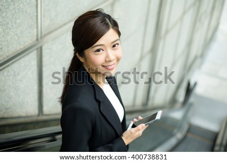 Businesswoman going down escalator