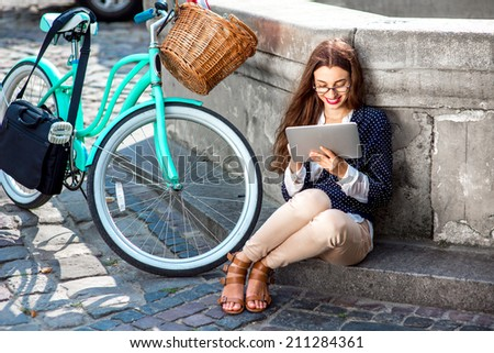 Businesswoman going to work by bicycle speaking phone in old city center background - stock photo