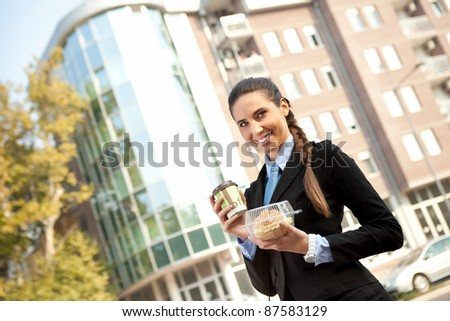 businesswoman going to work with breakfast in hand, outdoor - stock photo