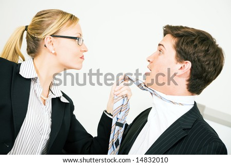 Businesswoman grabbing her colleague at his tie - stock photo