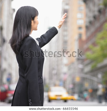 Businesswoman hailing a cab - stock photo