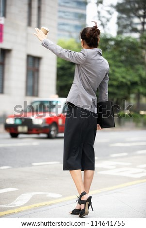 Businesswoman Hailing Taxi In Busy Street - stock photo