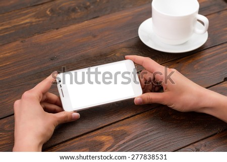 businesswoman hand holding a phone with isolated screen against the background of the table in the office - stock photo