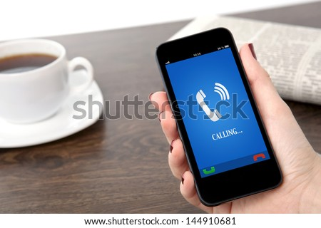 businesswoman hand holding a phone with ringing phone receiver on a screen against the background of a table in the office - stock photo