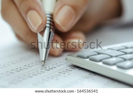 Businesswoman hand holding pen on spreadsheet - stock photo