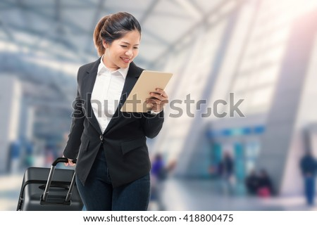businesswoman hand holding tablet while carrying luggage with airport background - stock photo