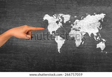 businesswoman hand represent on classroom media continents over black board - stock photo