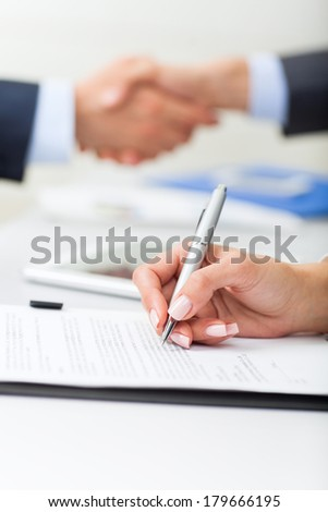 Businesswoman hand sign up contract document at office desk, businessman handshake  during meeting,  business people close up signing agreement - stock photo