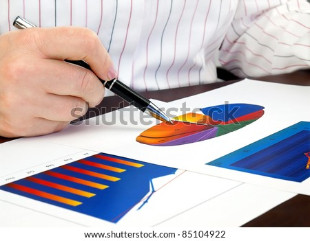 Businesswoman hand with pen on the investment chart. - stock photo
