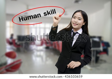 Businesswoman Hand writing human skill with black marker on visual screen. Isolated on gray background. Business, technology, internet concept. Stock Photo