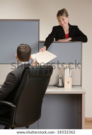 Businesswoman handing co-worker file folder at desk in cubicle - stock photo