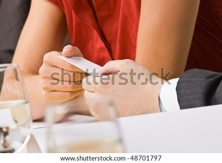 Businesswoman handing co-worker her business card - stock photo