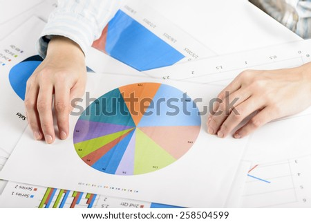Businesswoman hands analyzing financial statistics. Business woman Meeting Planning Analysis Statistics Brainstorming Concept. Analysis of financial reports. A woman pointing at a colorful chart graph - stock photo