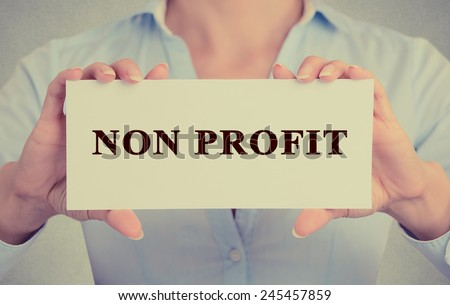 Businesswoman hands Holding Small White Sign card with Non Profit Text message  - stock photo