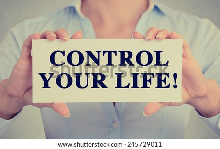 Businesswoman hands holding white card sign with control your life text message isolated on grey wall office background. Retro instagram style image - stock photo