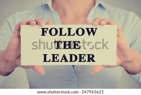 Businesswoman hands holding white card sign with follow the leader text message isolated on grey wall office background. Retro instagram style image - stock photo