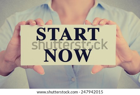 Businesswoman hands holding white card sign with start now text message isolated on grey wall office background. Retro instagram style image - stock photo