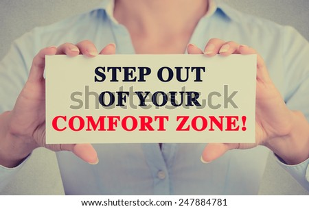 Businesswoman hands holding white card sign with step out of your comfort zone text message isolated on grey wall office background. Retro instagram style image - stock photo