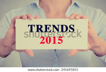 Businesswoman hands holding white card sign with trends 2015 text message isolated on grey wall office background. Retro instagram style image - stock photo