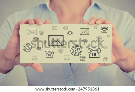 Businesswoman hands holding white card sign with variety of different contact icons for mail, email, web and telephone message isolated on grey wall office background. Retro instagram style image - stock photo