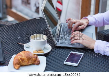 Businesswoman hands with laptop and mobile phone during breakfast. - stock photo