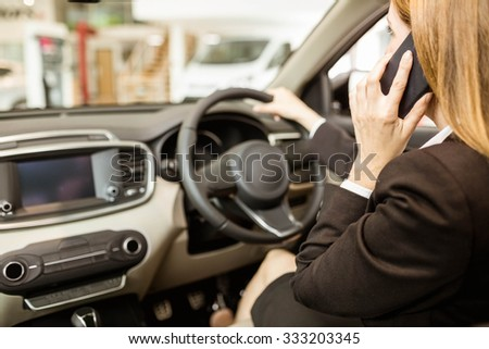 Businesswoman having a phone call while siting in a car at new car showroom