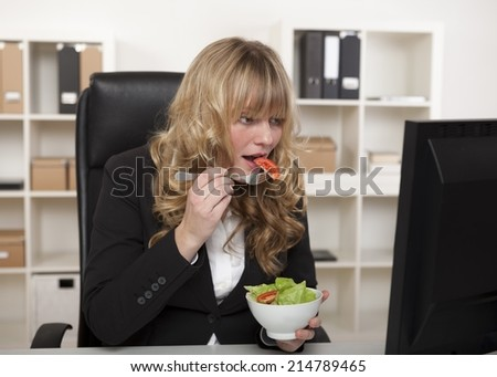 Businesswoman having a quick snack at her desk eating a healthy green salad as she continues reading information on her computer monitor - stock photo