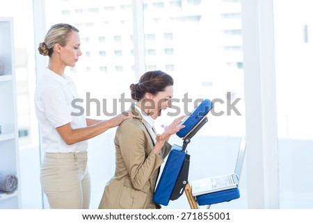 Businesswoman having back massage while using her laptop in medical office - stock photo