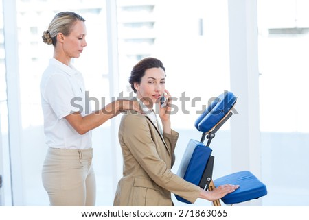 Businesswoman having back massage while using her mobile phone in medical office - stock photo