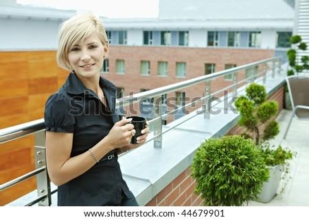 Businesswoman having break on office terrace outdoor drinking coffee. - stock photo