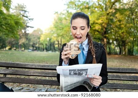 businesswoman having breakfast in park - stock photo