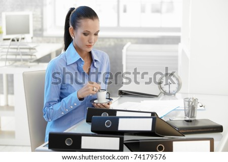 Businesswoman having coffee break at office desk.? - stock photo