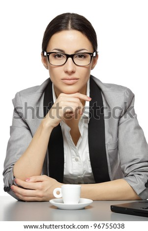 Businesswoman having coffee break, sitting at her office desk, over white background