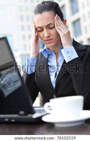 businesswoman having headache in front of her laptop, expression face - stock photo