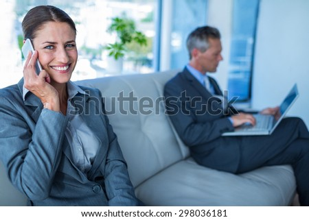 Businesswoman having phone call while her colleague using laptop in office - stock photo