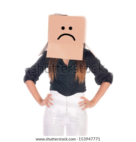Businesswoman hiding under a cardboard box with sad face.