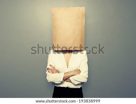 businesswoman hiding under empty paper bag over dark background - stock photo