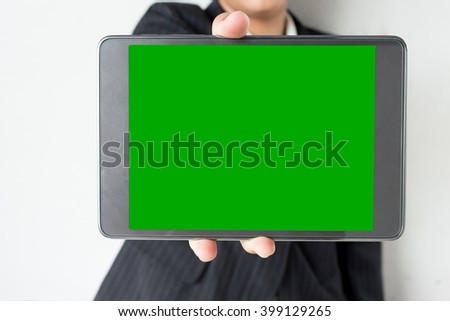 businesswoman hold green screen on Tablet - stock photo