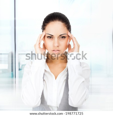 Businesswoman hold hands on temples head, young attractive business woman concept of business man stressed, headache, depressed, pain in modern office - stock photo