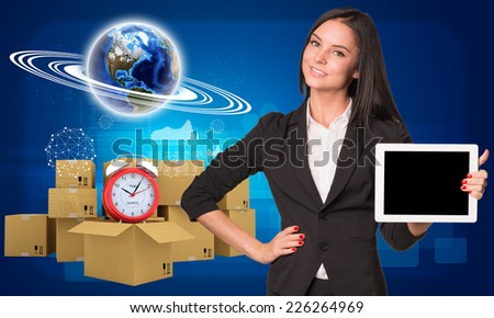 Businesswoman hold tablt pc with empty screen. Earth and heap of cardboard boxes with alarm clock as backdrop. Element of this image furnished by NASA - stock photo